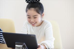 タブレットを操作する女の子の写真素材 [FYI04498061]