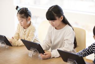 タブレットを操作する女の子の写真素材 [FYI04498070]
