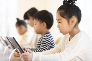 タブレットを操作する子どもたちの写真素材 [FYI04498086]
