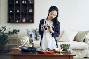 料理をカメラで撮影する40代日本人女性の写真素材 [FYI04498119]