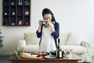 料理をカメラで撮影する40代日本人女性の写真素材 [FYI04498122]