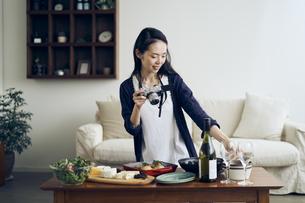 料理をカメラで撮影する40代日本人女性の写真素材 [FYI04498133]