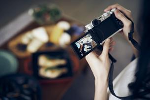 料理をカメラで撮影する女性の写真素材 [FYI04498139]