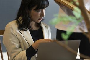 カフェで仕事をする女性の写真素材 [FYI04498162]