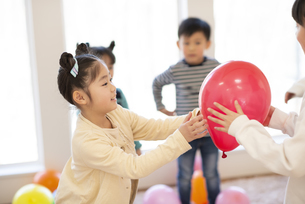 風船で遊ぶ子供たちの写真素材 [FYI04498175]