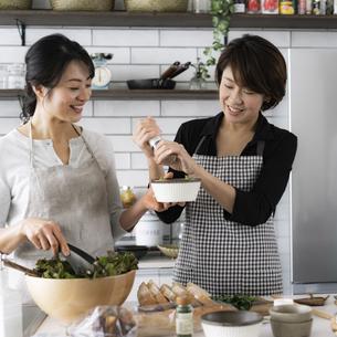 料理をする40代日本人女性2人の写真素材 [FYI04498304]