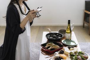 料理をカメラで撮影する女性の写真素材 [FYI04498313]