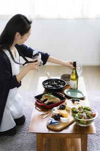 料理をカメラで撮影する女性の写真素材 [FYI04498314]