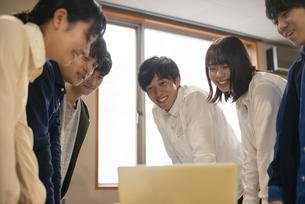 パソコンの前に集まる学生の写真素材 [FYI04498345]