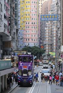 香港・ワンチャイ(湾仔)の街を行く路面電車トラム。トラムは英国植民地時代から走り続ける香港庶民の足の写真素材 [FYI04498369]
