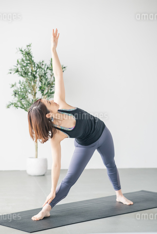 Woman practicing yoga in studio.の写真素材 [FYI04498490]