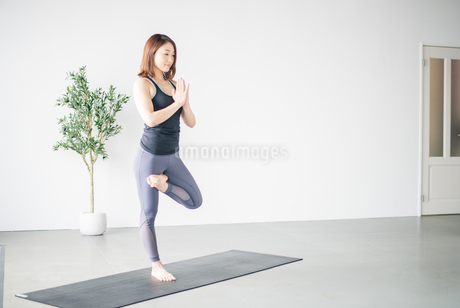 Woman practicing yoga in studio.の写真素材 [FYI04498491]