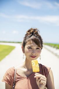 アイスを持つ笑顔の20代女性の写真素材 [FYI04498776]