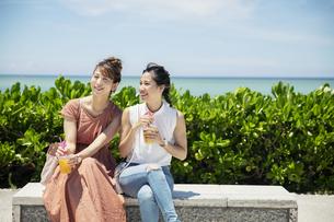 ベンチに座り話す20代女性2人の写真素材 [FYI04498777]