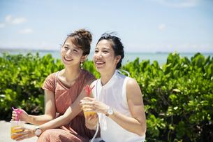 ベンチに座り話す20代女性2人の写真素材 [FYI04498779]
