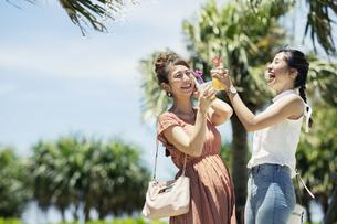 ジュースを持つ笑顔の20代女性の写真素材 [FYI04498786]