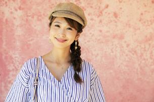 ピンクの壁の前に立つ20代女性の写真素材 [FYI04498791]