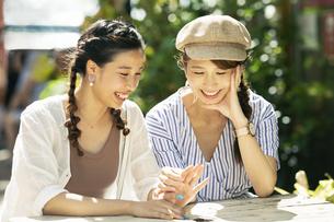 笑顔で話す20代女性2人の写真素材 [FYI04498794]