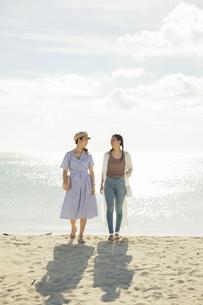 砂浜を歩く20代女性2人の写真素材 [FYI04498806]