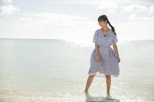 波打ち際で笑顔の20代女性の写真素材 [FYI04498823]
