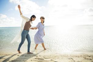 砂浜を歩く20代女性2人の写真素材 [FYI04498838]