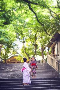 階段で遊ぶ浴衣姿の女の子の写真素材 [FYI04499449]