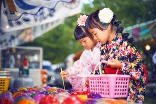 祭りでヨーヨー釣りをする浴衣姿の女の子の写真素材 [FYI04499468]