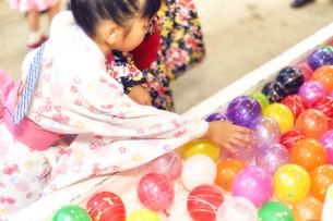 祭りでヨーヨー釣りをする浴衣姿の女の子の写真素材 [FYI04499472]