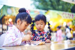 祭りの屋台で買ったたこ焼きを食べる浴衣姿の女の子の写真素材 [FYI04499476]