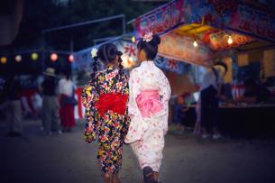 祭りの屋台を見回る浴衣姿の女の子の写真素材 [FYI04499479]