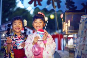 祭りの屋台で買ったかき氷を食べる浴衣姿の女の子の写真素材 [FYI04499480]