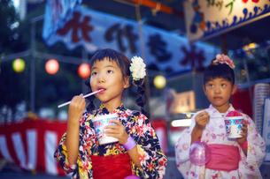 祭りの屋台で買ったかき氷を食べる浴衣姿の女の子の写真素材 [FYI04499481]