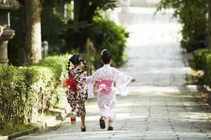 浴衣姿の2人の女の子の走る後ろ姿の写真素材 [FYI04499515]