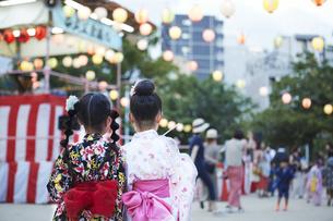 盆踊り会場を眺める浴衣姿の女の子の写真素材 [FYI04499617]