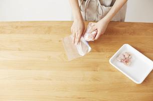 鶏肉を保存袋に入れる女性の写真素材 [FYI04499772]
