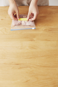 鶏肉の入った保存袋にメモを貼る女性の写真素材 [FYI04499773]