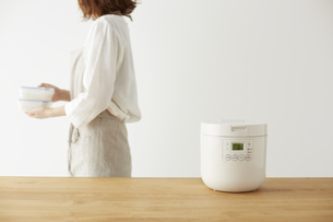 炊飯器とタッパーを持って横切る女性の写真素材 [FYI04499787]