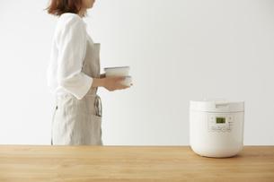 炊飯器とタッパーを持って横切る女性の写真素材 [FYI04499788]