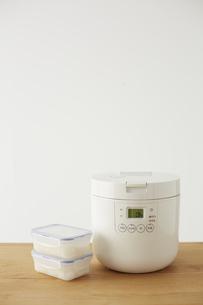 炊飯器とタッパーに小分けされた白ご飯の写真素材 [FYI04499790]