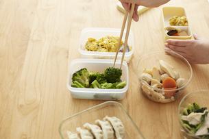 タッパーに入った食材を弁当箱に詰める女性の写真素材 [FYI04499808]