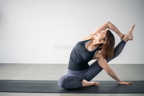 Woman practicing yoga in studio. Yoga exercise image.の写真素材 [FYI04500112]
