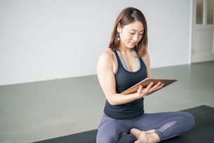 Woman watching yoga online tutorial.の写真素材 [FYI04500374]
