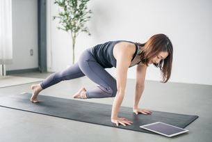 Woman watching yoga online tutorial.の写真素材 [FYI04500375]