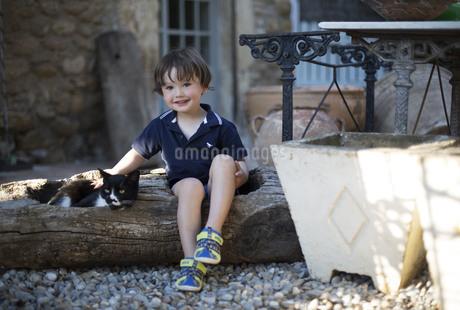ハーフの幼児が屋外で黒白の猫を撫でている様子の写真素材 [FYI04500438]