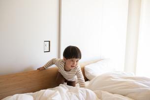 ベッドの上に乗って遊ぶ小さな男の子の写真素材 [FYI04500607]