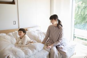 ベッドの上で遊ぶ小さな男の子とそれを見守る母親の写真素材 [FYI04500610]