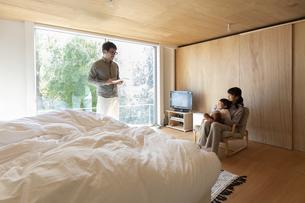 寝室で会話する3人家族の写真素材 [FYI04500616]