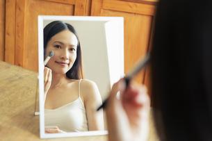 部屋で鏡を見ながら化粧をする20代女性の写真素材 [FYI04501425]