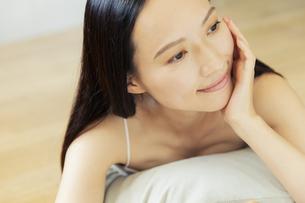 部屋でくつろぐ笑顔の20代女性の写真素材 [FYI04501432]
