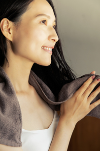 お風呂上がりで窓の外を眺める笑顔の20代女性の写真素材 [FYI04501440]